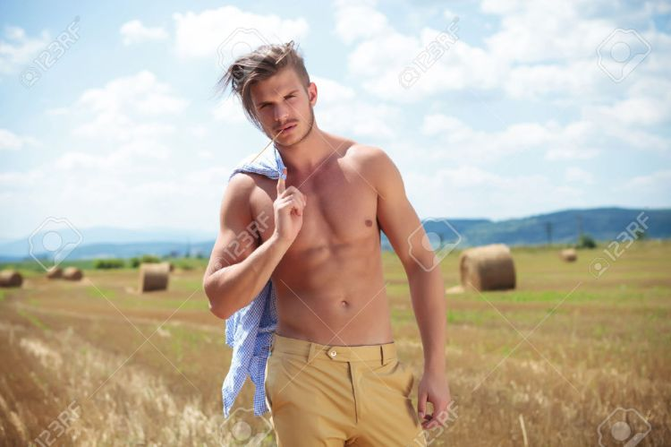 22995219-young-topless-man-posing-outdoor-on-a-cereal-field-with-a-straw-in-his-mouth-while-holding-his-shirt-Stock-Photo
